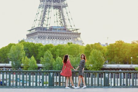 Beautiful twin sisters in front of the Eiffel tower in Paris