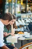 Mladý romantický pár s mapou ve francouzské kavárně