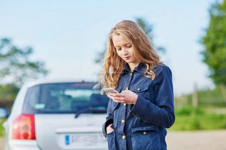 Photo for Young woman on the road near a broken car calling for help - Royalty Free Image