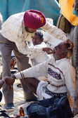 Sikh dentist treats teeth of old man without during traditional camel fair holiday at Pushkar,Thar desert,India