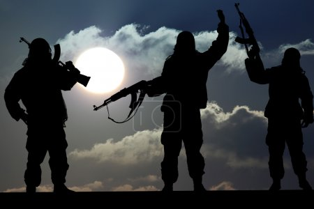 Photo for Silhouette of military soldier or officer with weapons at sunset. shot, holding gun, colorful sky, Concept of a terrorist. Silhouette terrorists with rifle at sunset - Royalty Free Image