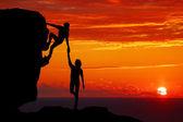 """Постер, картина, фотообои """"Команде пара Пешие прогулки помощь друг другу доверять помощи силуэт в горах, закат. Совместной работы мужчины и женщины турист, помогая друг другу на вершине горного восхождения группы"""""""