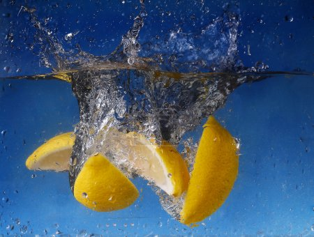 Whole lemon dropped in water against gradient blue...