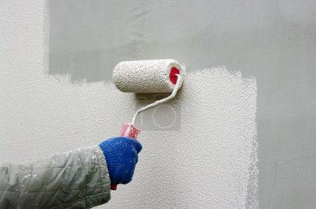 Foto de Pintar a mano una pared blanca con un rodillo de pintura - Imagen libre de derechos