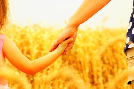 Photo pour Les mains de la mère et de la fille se tenant sur le terrain - image libre de droit