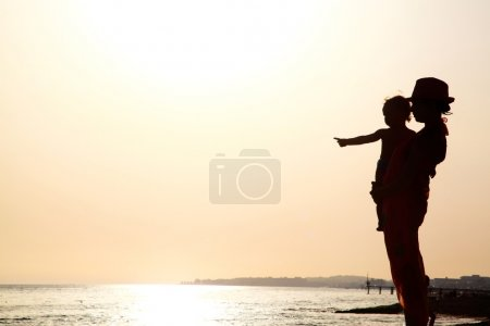 Photo for Woman with baby on the beach at the sunset - Royalty Free Image