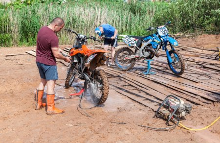 Man washing a race bike after the competition in motocross