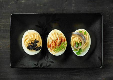 Various boiled stuffed eggs on black plate, top vi...
