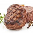 Grilled beef steaks with spices isolated on white ...