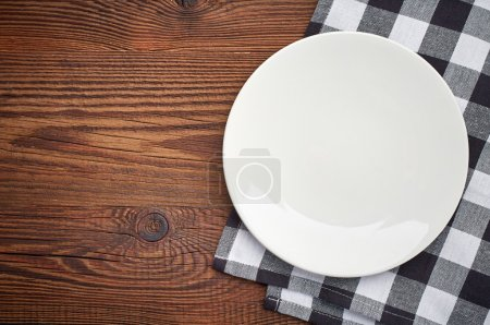Photo for Napkin and white plate on brown wooden table, top view - Royalty Free Image
