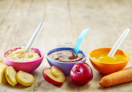 Foto de Varios tipos de alimentos para bebés en cuencos de plástico - Imagen libre de derechos