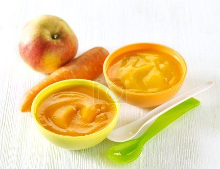 Foto de Various kinds of baby food in plastic bowls - Imagen libre de derechos