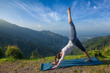 Photo pour Jeune femme en forme sportive faisant du yoga asana Adho mukha svanasana - variation vers le bas pour chien en plein air en Himalaya le matin - image libre de droit