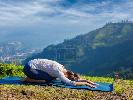Photo for Sporty fit woman practices yoga asana Balasana - child pose outdoors in mountains - Royalty Free Image