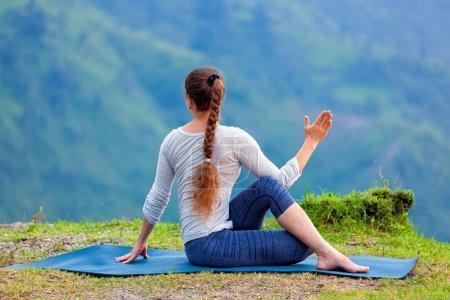 Woman practices yoga asana outdoors