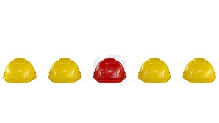 Línea de cascos de seguridad amarillos con uno rojo