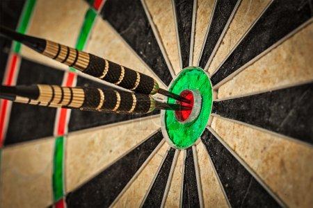 Three darts in bulls eye close up