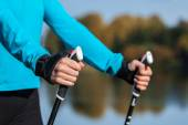 Closeup of womans hand with nordic walking poles