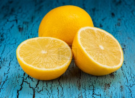 Photo for Lemon and cut half slice on blue wooden background - Royalty Free Image