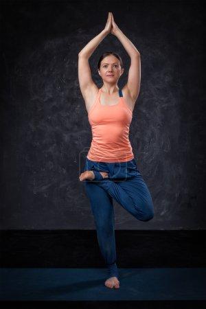 Woman practices yoga asana Vrikshasana tree po