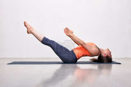 Woman practices yoga asana Uttana padasana
