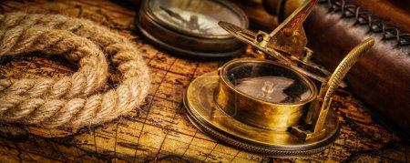 Photo pour Géographie du voyage arrière-plan du concept de navigation panorama de l'ancienne boussole rétro vintage avec cadran solaire, verre espion et corde sur la carte du monde antique - image libre de droit