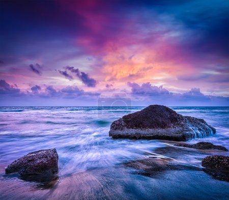 Photo pour Fond de vacances plage tropicale - vagues et rochers sur la plage sur coucher de soleil avec belle cloudscape - image libre de droit