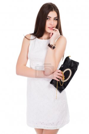 Woman posing in white dress with purse