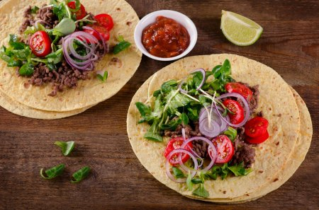 Two mexican tacos on wooden table