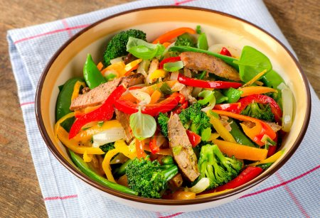 Beef stir fry with vegetables and herbs. Selective focus