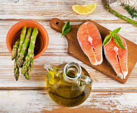 Photo for Healthy food  ingredients on a wooden table - salmon, vegetables , lemon and olive oil - Royalty Free Image