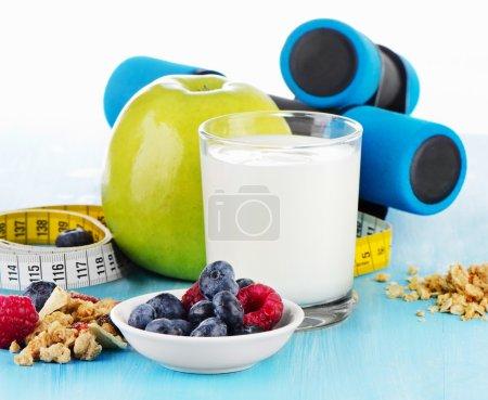 Photo pour Haltères avec des aliments sains et des boissons sur une boulangerie bleue. Concentration sélective - image libre de droit