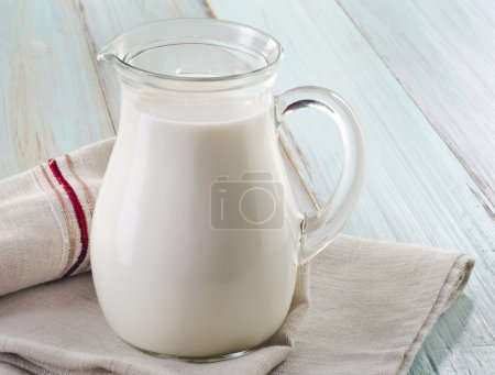 A jug of cow milk on wooden table...