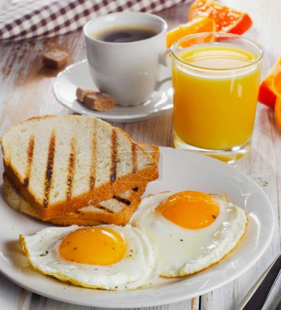 Photo for Breakfast with two fried eggs, toasts, juice and coffee. Selective focus - Royalty Free Image
