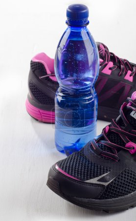 Running shoes and bottle of water - healthy lifestyle