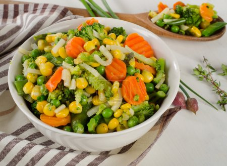 Mixed vegetables with herbs in white bowl.