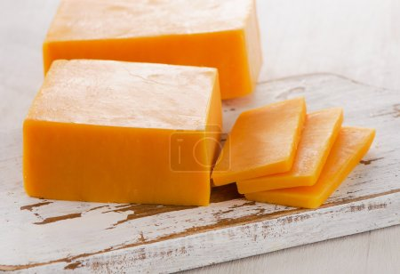 Photo for Cheddar Cheese on  white wooden Cutting Board. Selective focus - Royalty Free Image