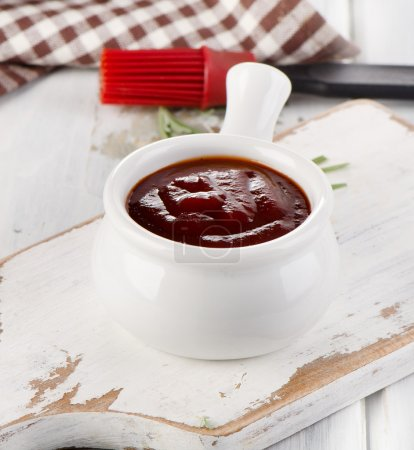 Photo for BBQ sauce in a white bowl with a brush and  fresh rosemary - Royalty Free Image