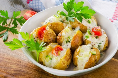 Photo for Hot baked potatoes with vegetables and sour cream. Selective focus - Royalty Free Image