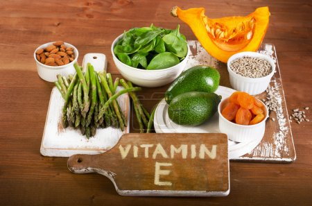 Foods containing vitamin E on a wooden board. View...