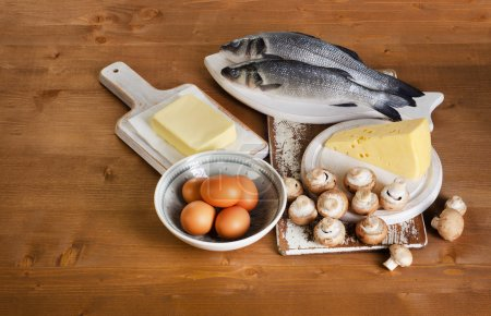 Foods containing vitamin D on a wooden table. View...