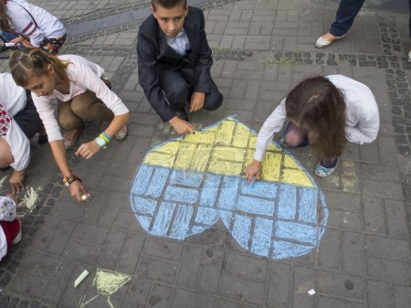 """Photo for The action began with patriotic drawings on asphalt. A dozen children of all ages, dressed in embroidered, painted on the square near the monument to the flags of Ukraine and the yellow-blue heart, and wrote the national motto, """"Glory to Ukraine!"""". - - Royalty Free Image"""
