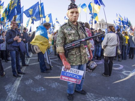 Photo pour KIEV , UKRAINE - October 14, 2014: A man wearing a mask of President Vladimir Putin in uniform with a gun on his chest and bloody hands. - image libre de droit