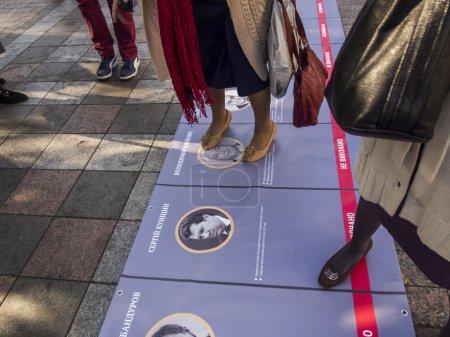 Photo pour Kiev , Ukraine - 14 octobre 2014:Les femmes piétinaient des portraits de politiciens corrompus près de Verkhovna Rada. -- Sur la place de l'Indépendance, dans le centre-ville de Kiev, environ 2 000 militants ont exigé la reconnaissance des soldats de l'armée insurgée ukrainienne - image libre de droit