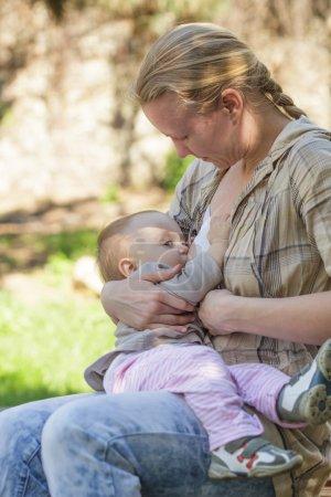 Mother breastfeeds baby