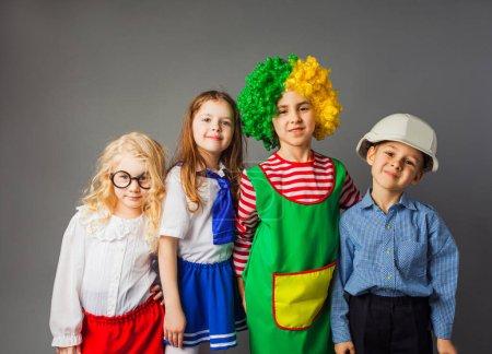 Photo pour Le groupe d'enfants dans un costume de professions différentes restent à l'arrière-plan gris. Les enfants sourient et regardent la caméra - image libre de droit
