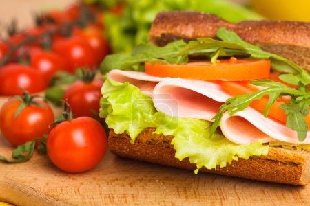 Photo for Wholegrain sandwich with ham, tomato, lattuce and arugula with glass of orange juice. Breakfast - Royalty Free Image