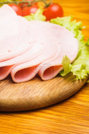 Photo for Fresh ham slices with lattuce and cherry tomato on the wooden board - Royalty Free Image