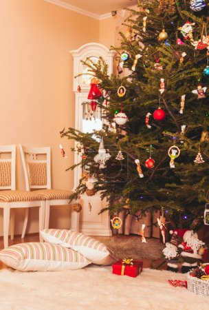 Photo for Christmas tree with presents underneath  of Santa Claus and two pillows lying along - Royalty Free Image