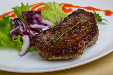 Photo for Grilled beef steak with onion and basil leaves - Royalty Free Image